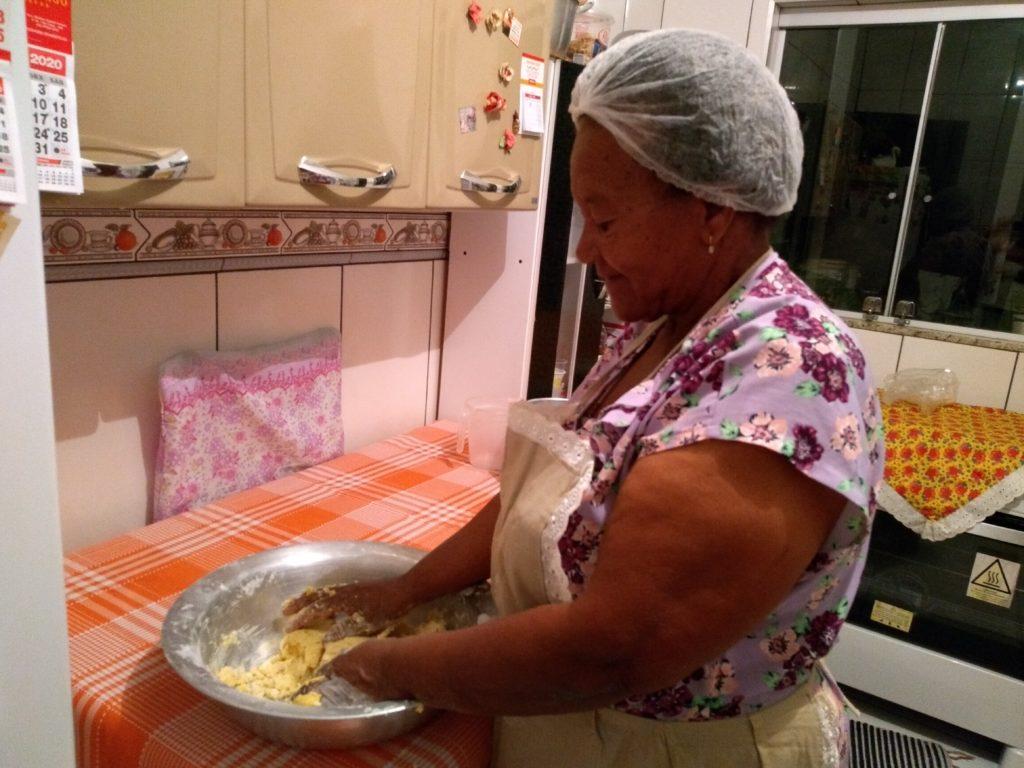 Em uma bacia de inox, Dona Conceição sova bem a massa do biscoito.