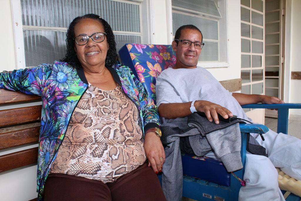 A foto mostra o professor João Batista Augusto sentado em uma cadeira confortável, na UCCI, ao lado da sua tia Dalva, que o acompanha no tratamento.