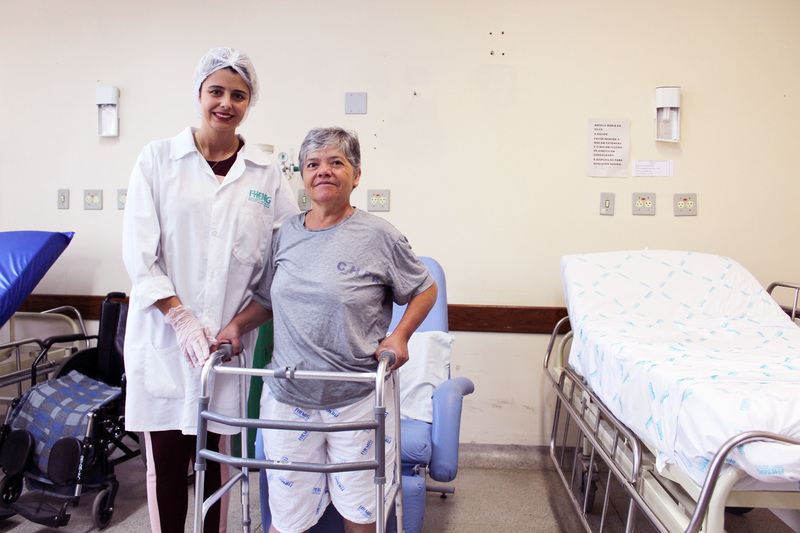 Uma enfermeira acompanha a paciente Ângela que, após 15 dias de tratamento, já se locomove com o auxílio de andador ortopédico.