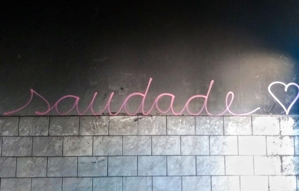 """Em uma parede metade azulejo, metade cimento batido, aparece a palavra """"saudade""""."""