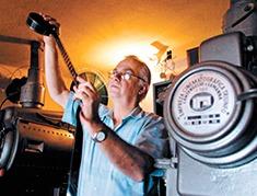 O dono do cinema, au lado do projetor, examinando um filme de rolo.