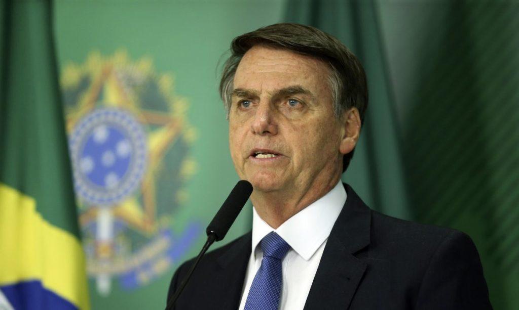 A foto mostra o presidente Jair Bolsonaro fazendo um pronunciamento, com a bandeira brasileira ao fundo