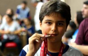 menino campeão em matemática com medalha na boca