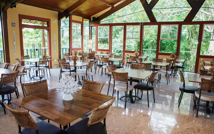 Visão do restaurante-escola de Tiradentes, com mesas amplas e janelas de vidro para espaço arborizado.