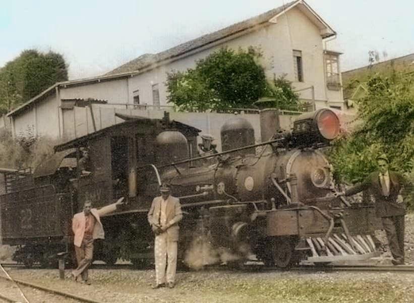 Foto histórica que mostra o antigo viradouro de trens de Barbacena, com a Maria Fumaça a frente, com o maquinista dentro da locomotiva e dois homens a frente dela.