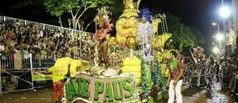 Mostra o carro abre alas da Bate Paus na avenida, nas cores verde e amarelo, com o destaque em cima e foliões no entorno.