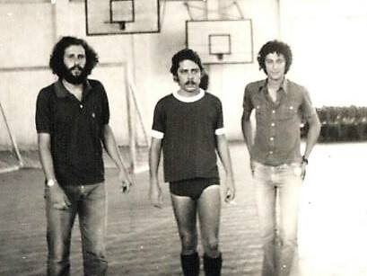 A foto mostra Chico Buarque de Hollanda, com calção e meião, entre duas pessoas, no ginásio Sílvio Raso, em Barbacena.